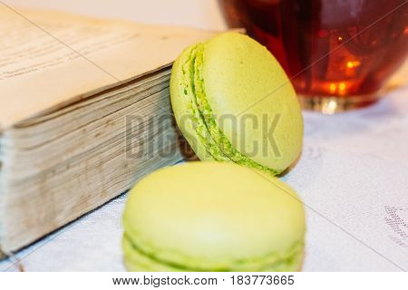 Two macarons dessert on a table near old books and a cup of black tea