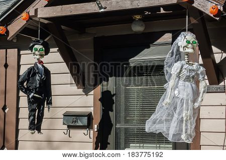 Skeleton bride and groom with bulging green eyes and smiles on their faces