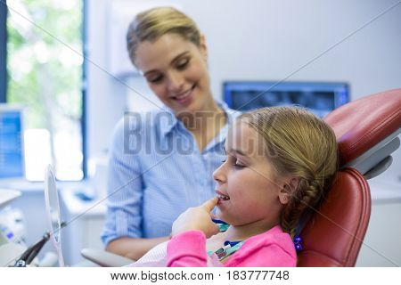 Young girl patient looking in the mirror at dental clinic