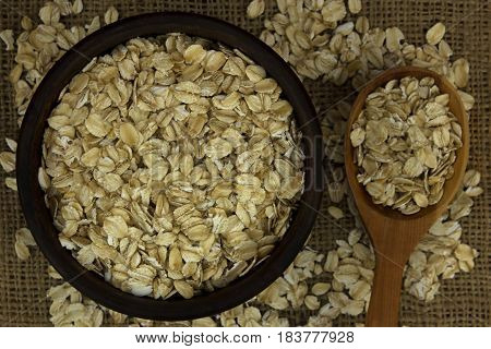 Dry oat flakes oatmeal in bowl on sacking with wooden spoon