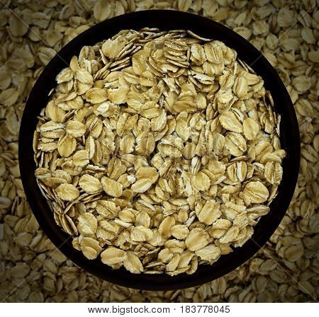 Dry oat flakes oatmeal in bowl on the background