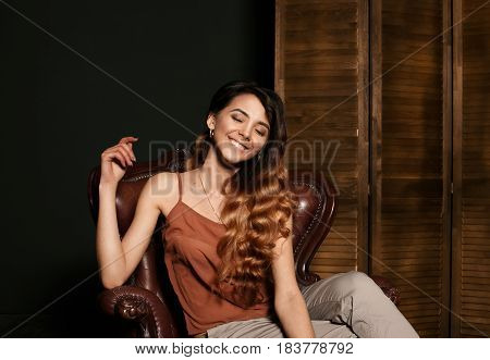 Smiling girl face. Fashionable portrait of fashionable girl with beautiful smile. Smiling gorgeous girl with perfect clean skin wavy colored hair. Smiling girl sitting in leather brown armchair