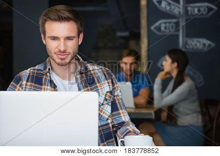 Man using laptop while having coffee in café