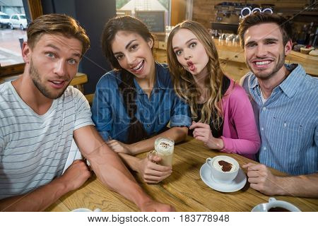 Portrait of happy friends making faces while having coffee in café