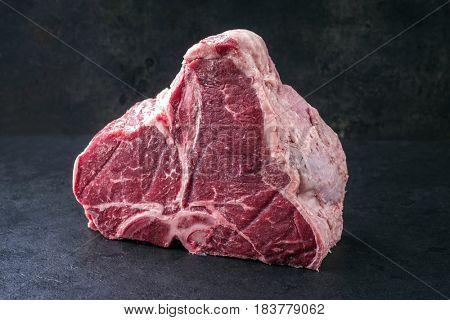 Raw dry aged Wagyu Porterhouse Steak as close-up on a black slate