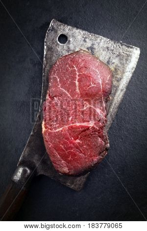 Dry aged raw Wagyu Point Steak as close-up on a kitchen cleaver