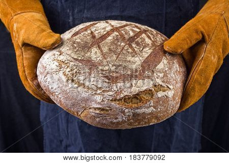 Freshly backed Farmhouse Bread hold in hand with oven gloves