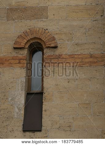 A small thin window with a sash down in an ancient church