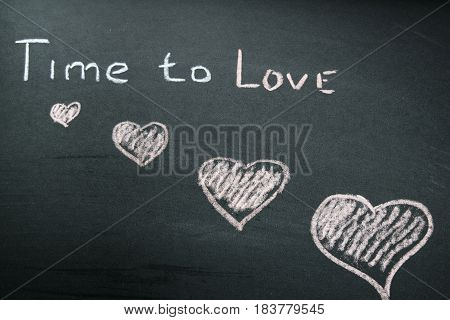 An inscription of time to love chalk on a slate background and a penciled heart