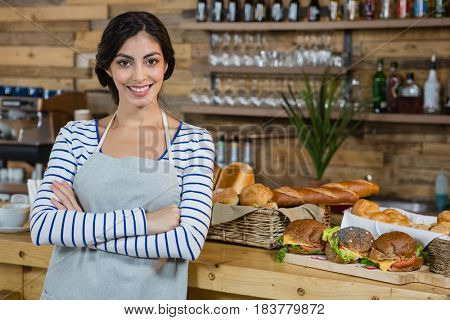 Portrait of waitress standing with arms crossed at counter in cafe