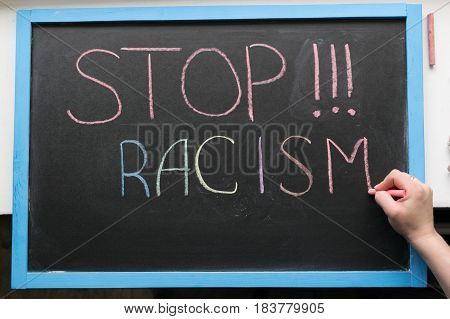 An inscription of stop racism with a multi-colored chalk on a slate in a blue frame and a hand with chalk that adds it