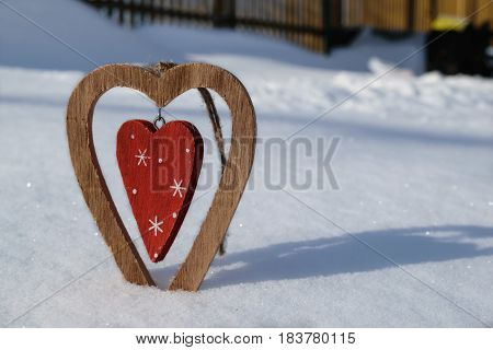 Vintage wooden heart which is in the middle of another wooden heart in red with snowflakes standing in the snow and drops beautiful shadow