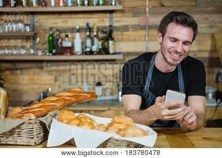 Waiter using mobile phone at counter in cafe