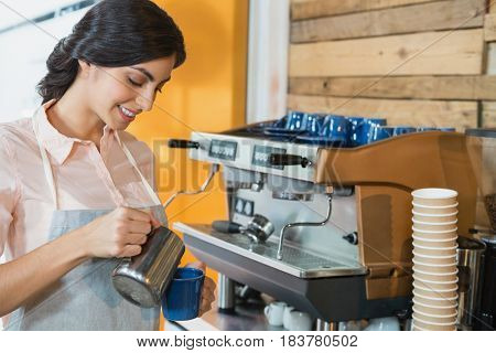 Waitress pouring coffee into cup in cafe