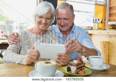 Happy senior couple using digital tablet in cafe