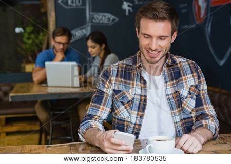 Man using mobile phone while having coffee in café