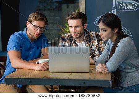 Friends using laptop while having coffee in café