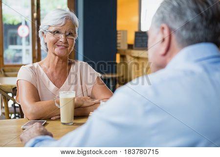 Senior couple interacting while having coffee in café
