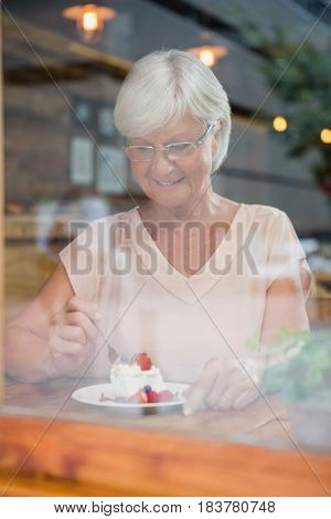 Senior woman having breakfast in cafe