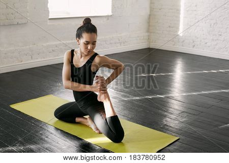 Handsome asian female student practicing Eka Pada Rajakapotasana yoga pose before classes at university early morning in order to better concentrate. Copy space for promotional text. Horizontal mockup