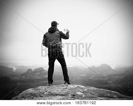 Man Takes Photos With Smart Phone On Peak Of Rock Empire. Melancholy Fog