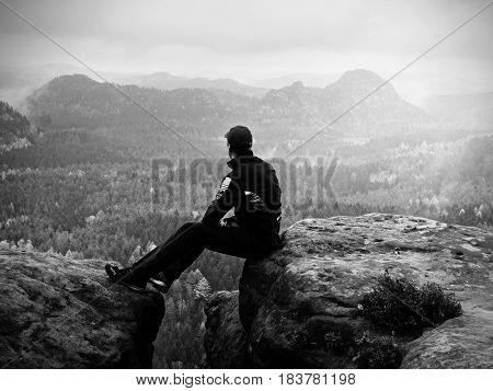 Man In Black Sit On Cracked Rocky Empires. Melancholy Misty Day