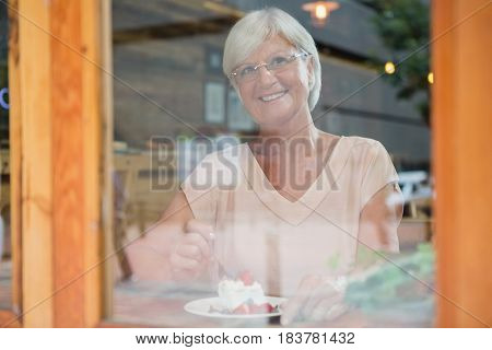 Thoughtful senior woman having breakfast in cafe