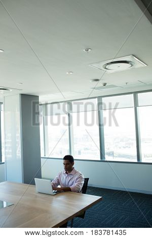 Businessman typing on laptop while sitting at table in conference room