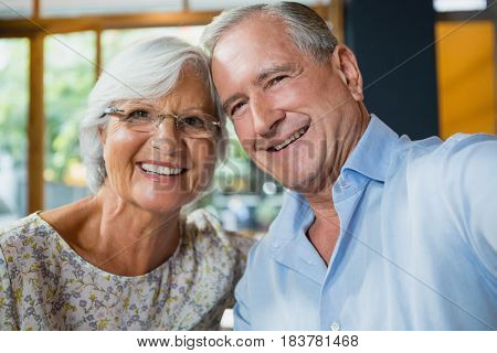 Portrait of happy senior couple sitting in cafe