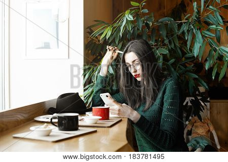 Adorable serious young woman dressed casually checking her news feed or messaging via social networks using free wi-fi on mobile phone sitting near the window against big plants in the coffee shop