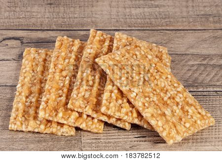 Group of sesame seed cookies on wooden plank.
