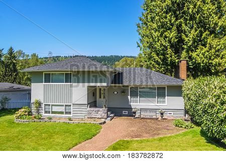 Average residential house with mowed loan on the front yard for sale. Simple residential house in North America with paved pathway to the entrance