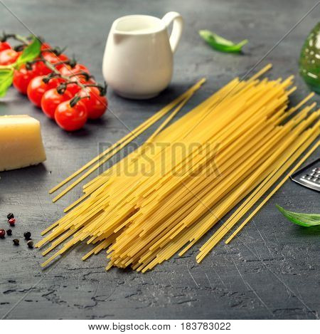 Italian raw pasta with a set of ingredients for cooking pasta on a dark surface