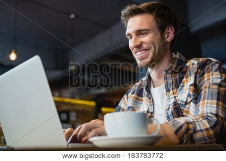 Young man using laptop while having coffee in cafe