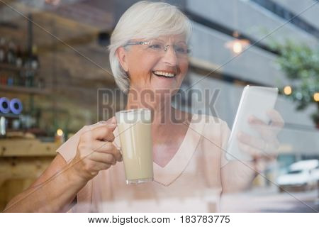 Happy senior woman using mobile phone while having cold coffee in cafe