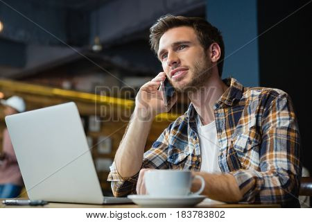 Young man talking on mobile phone while using laptop in cafe