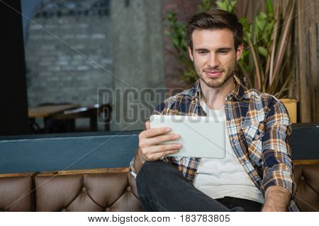 Young man using digital tablet while relaxing on sofa in cafe