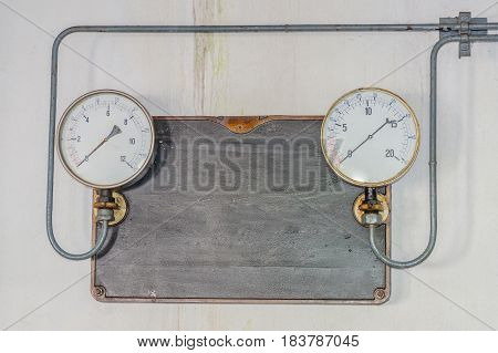 Two old pressure gauges on a metal plate made of cast iron with pressure supply lines from an old ice cream maker. Tex free space.