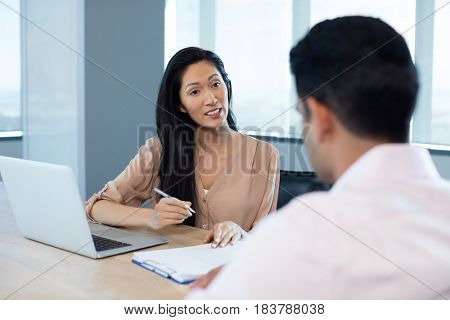 Businesswoman discussing contract with male colleague during meeting in office