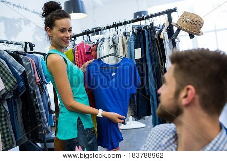 Woman showing clothes to man at clothes store