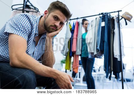 Bored man with shopping bags while woman by clothes rack at clothes store