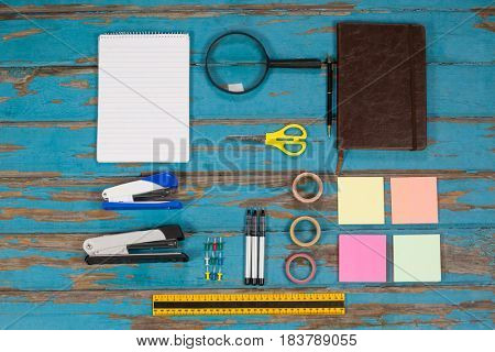 Notepad, stapler, pins, sellotapes, diary, sticky notes, ruler and pens on wooden plank