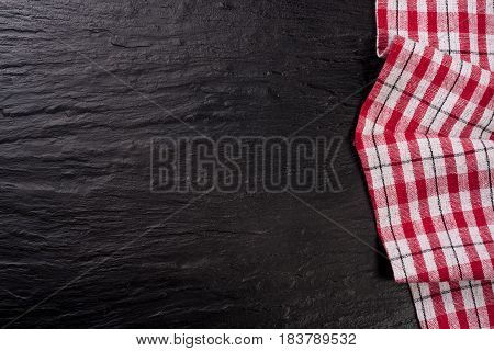 Red checkered tablecloth on a dark stone background with copy space for your text. Top view.