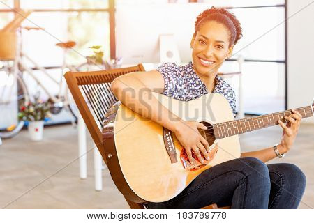 Portrait of smiling afro-american office worker sitting in offfice with guitar