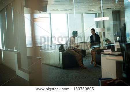Business colleagues interacting while sitting on sofa in office seen through glass