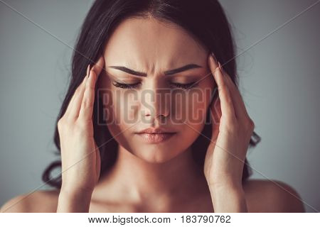 Portrait of beautiful young brunette with bare shoulders touching her temples feeling stress on gray background