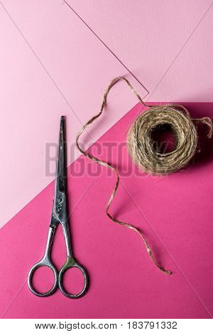 A photo of vintage scissors with a roll of twine on pink background