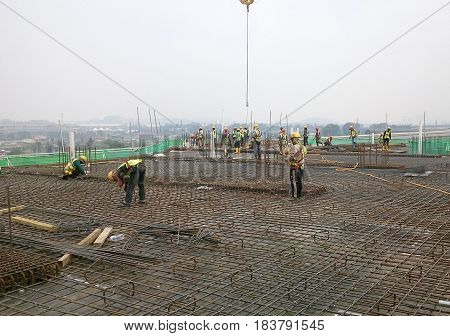 KEDAH, MALAYSIA -JANUARY 14, 2017: Construction workers fabricating steel reinforcement bar at the construction site in Kedah, Malaysia. The reinforcement bar was ties together using tiny wire.