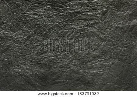 Black crumpled sheet of paper textured background with copy space for text or image.