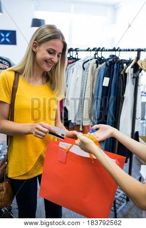 Beautiful women paying with credit card at clothes store